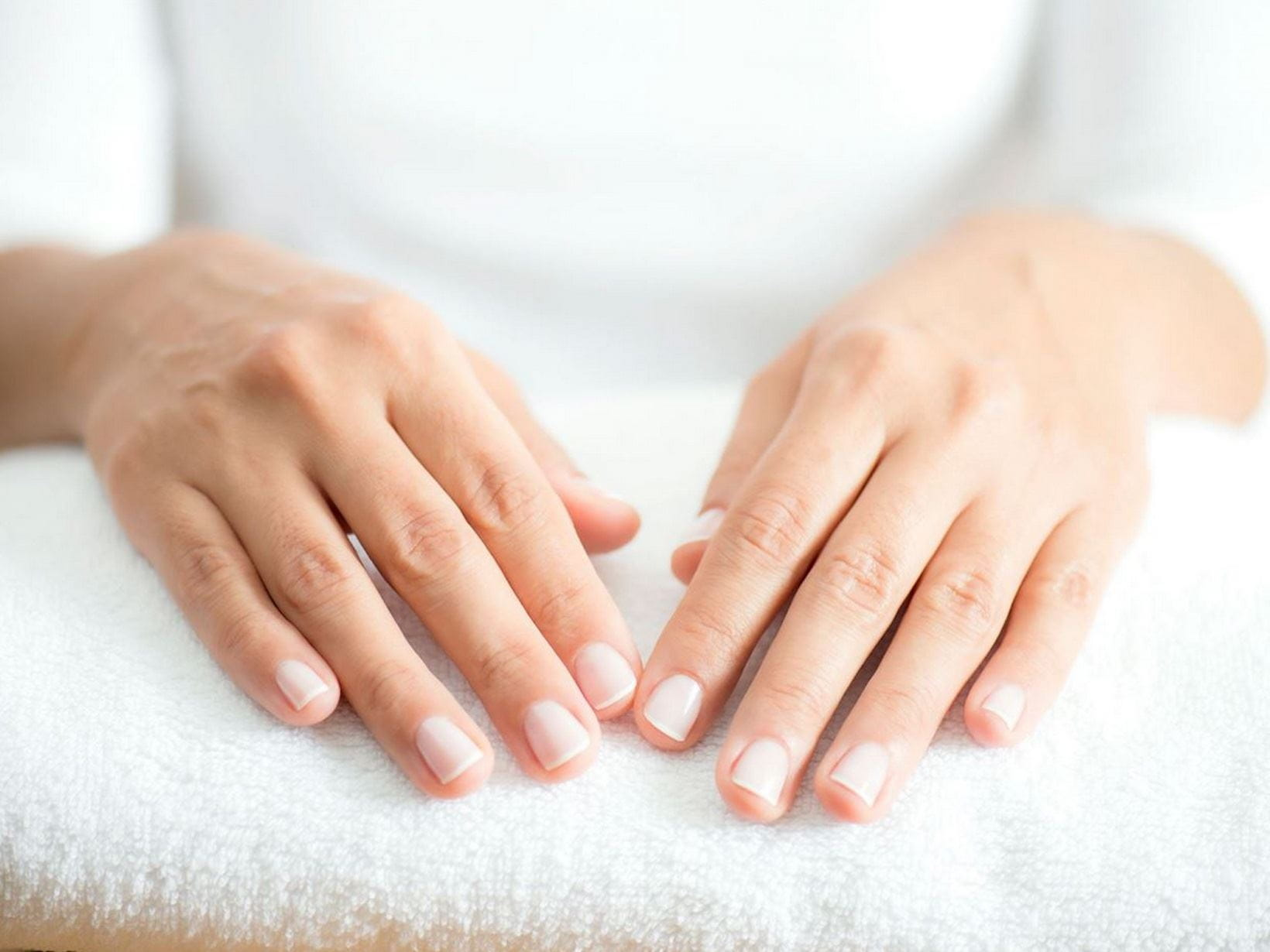 manicured hands on a white towel