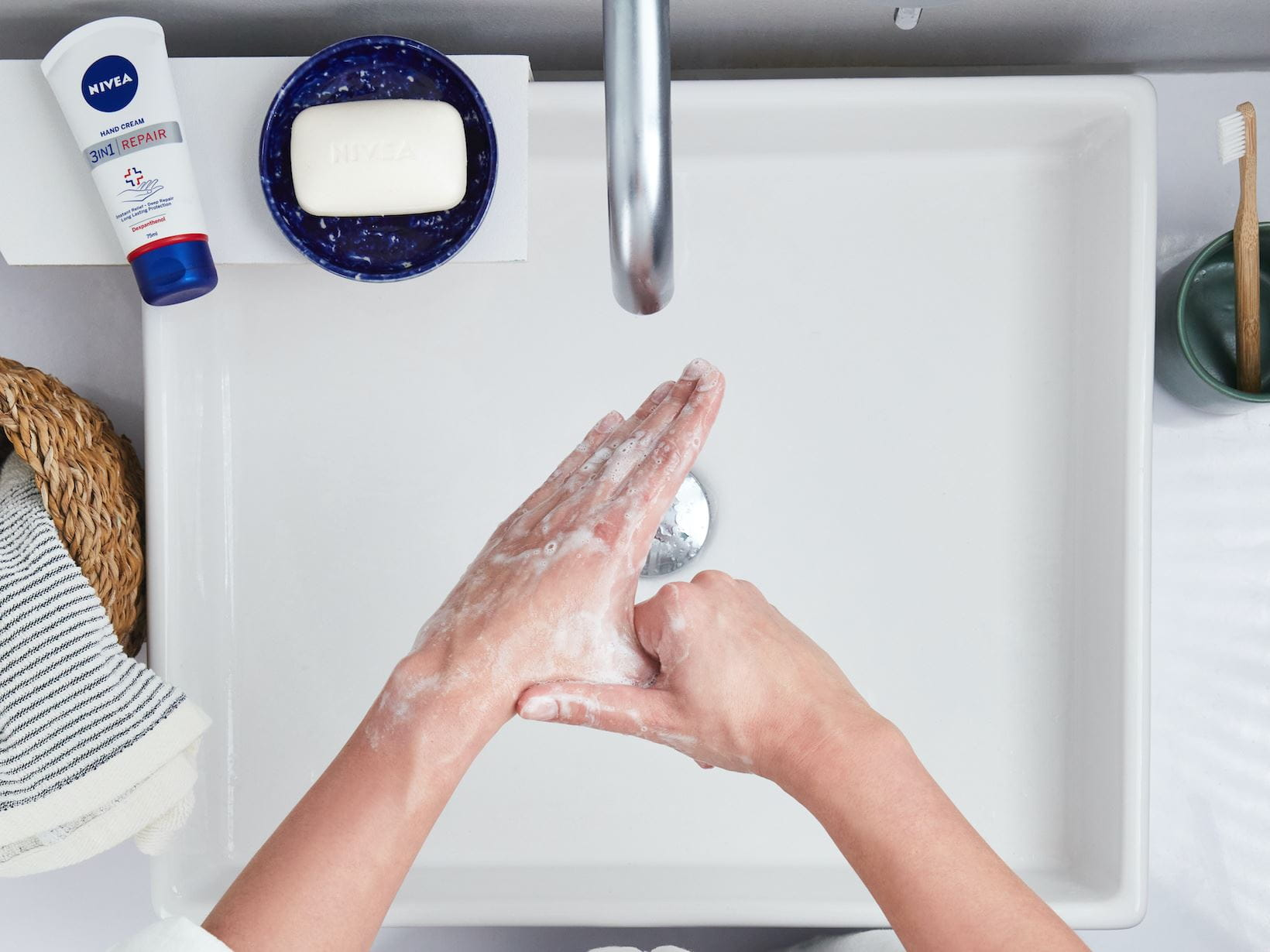 hands rubbing soap in between there fingers under a tap