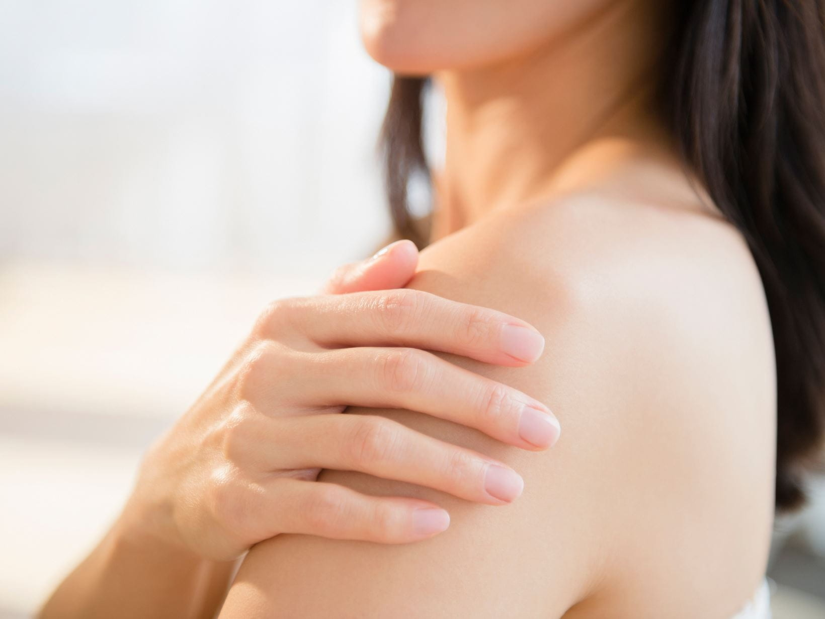lady touching the dehydrated skin on her shoulder