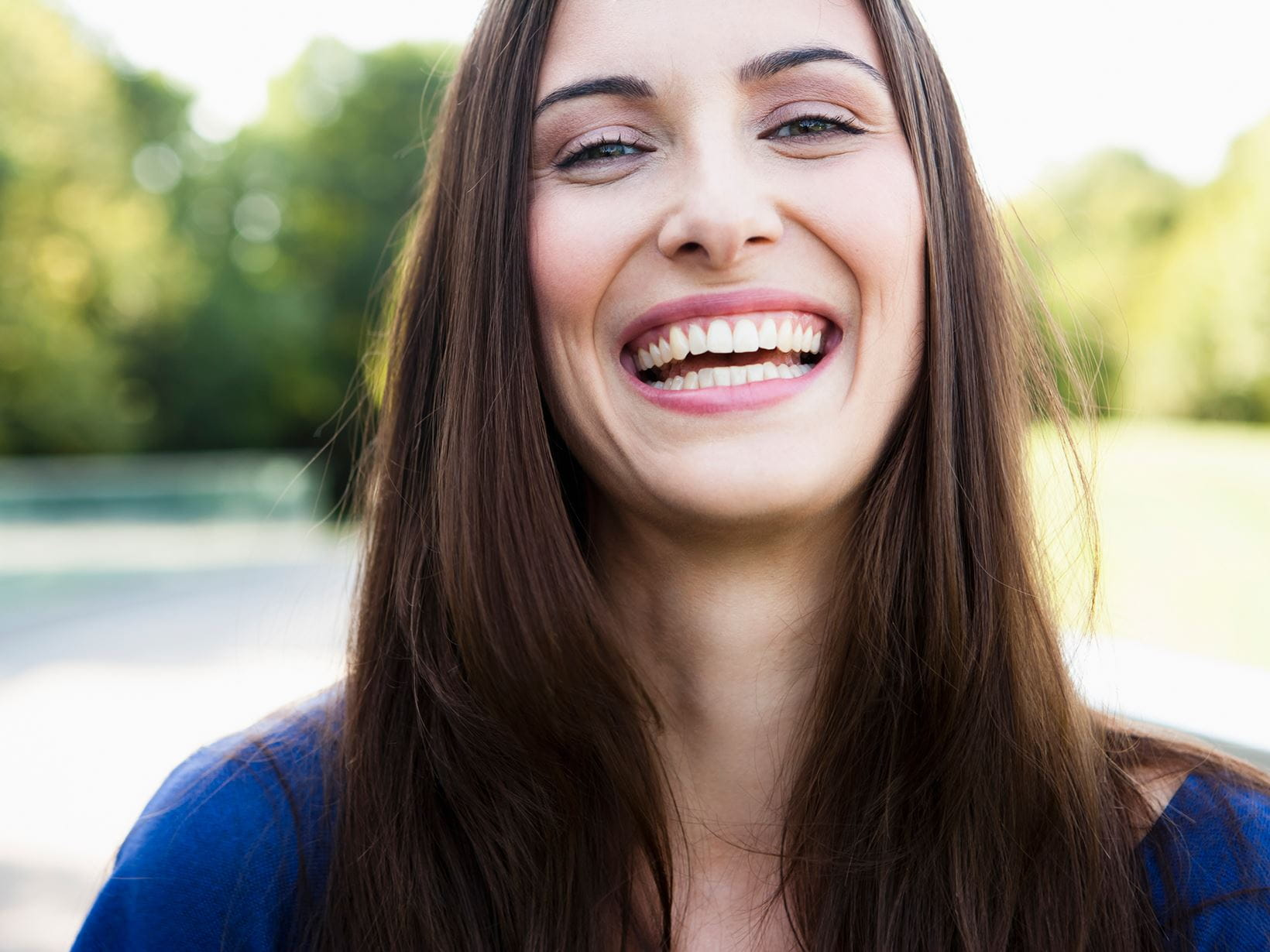 pretty brunette lady smiling wearing blue