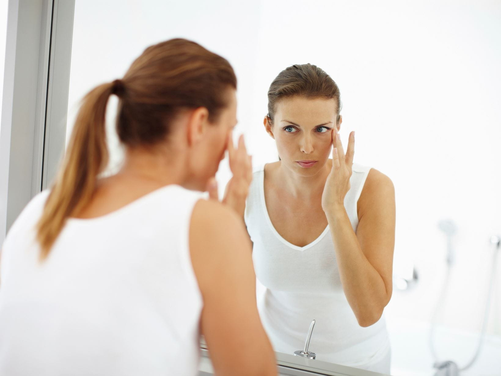 woman-skincare-in-front-of-bathroom-mirror