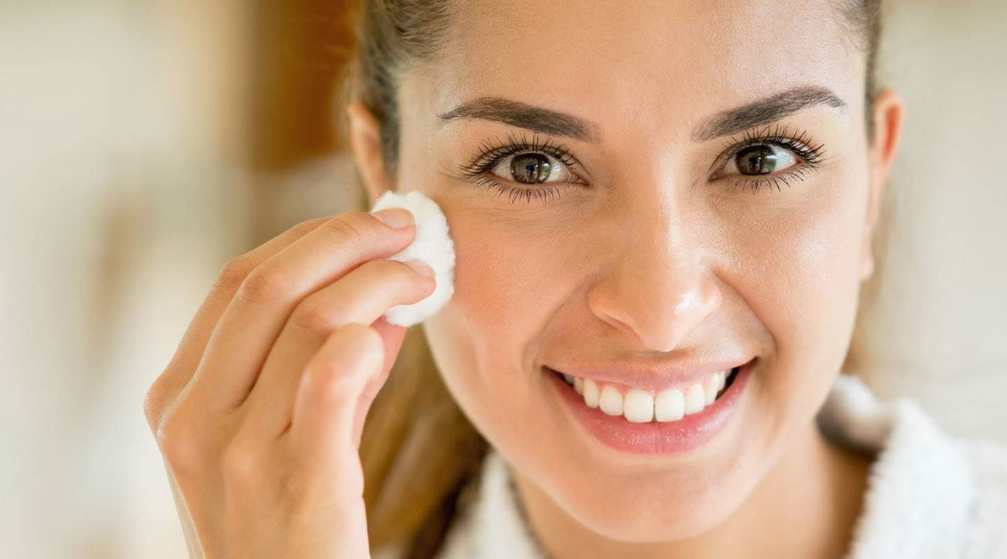 brunette lady using lactic acid skin on her face with a cotton pad