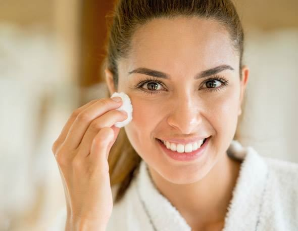lady with brunette hair using cotton pads to remove makeup