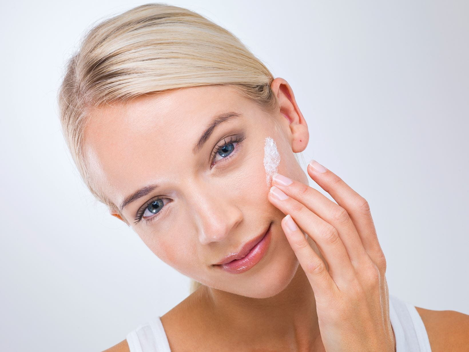 blonde lady applying face cream to soothe facial redness