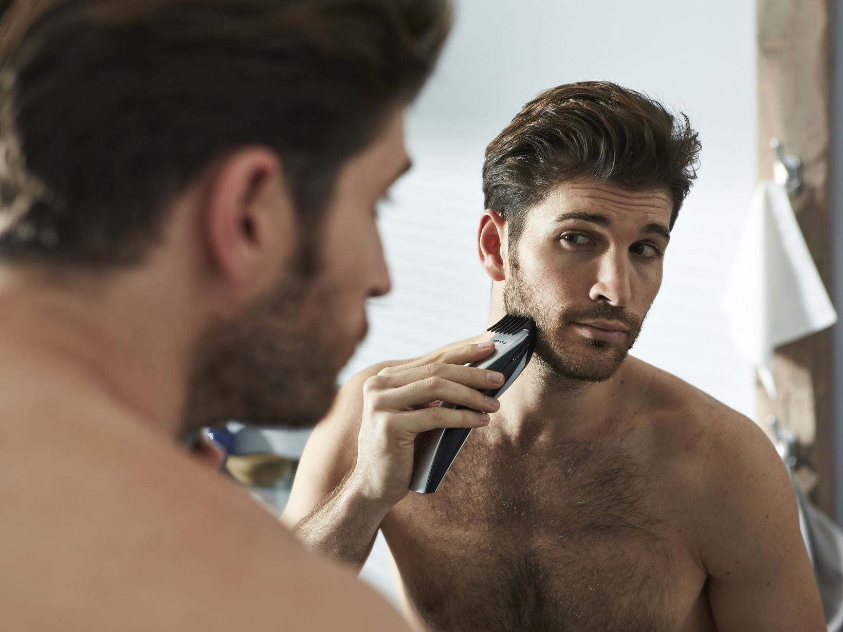 man shaping his 5 o'clock shadow in the mirror