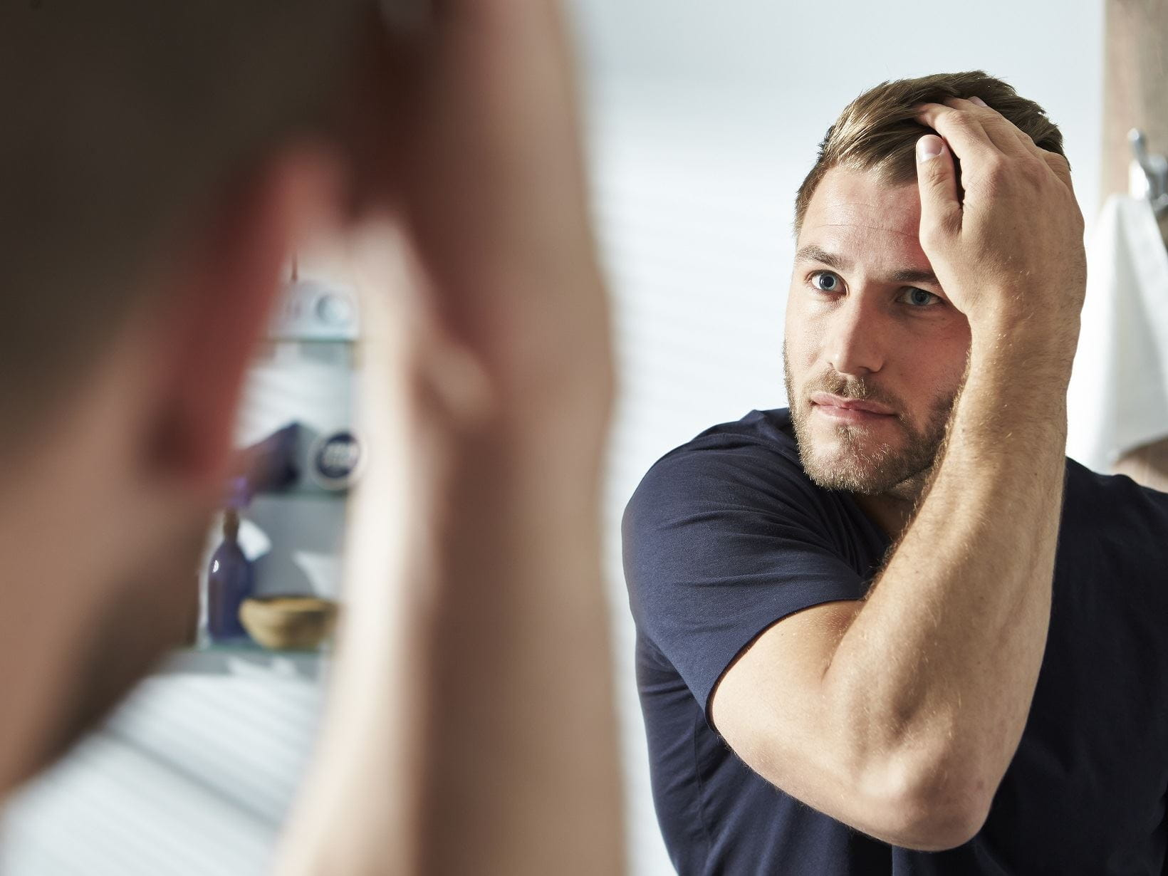 blonde haired man getting rid of his dandruff in front of a mirror