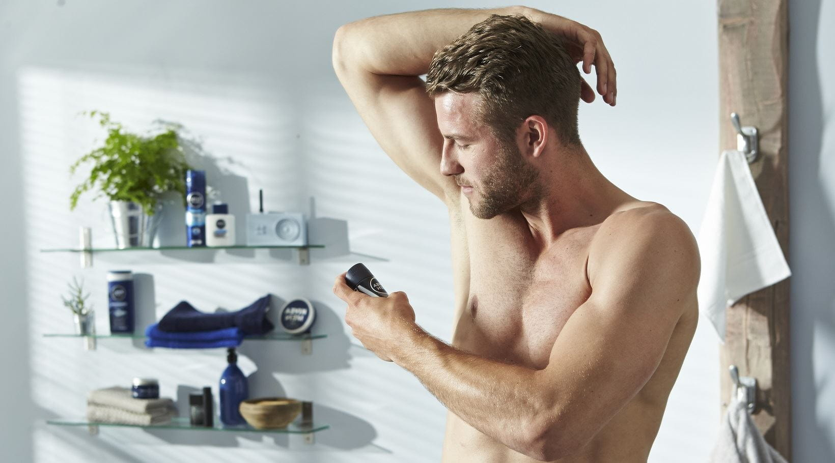 man using deodorant to stop armpit smell