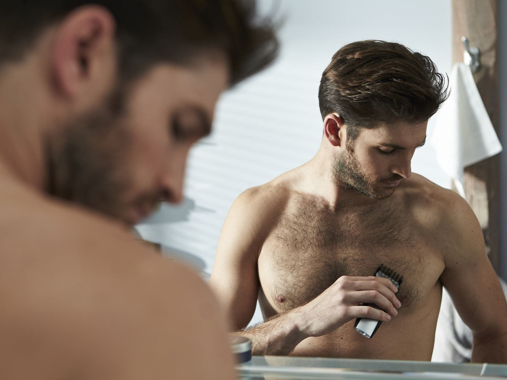man manscaping his chest hair with a razor