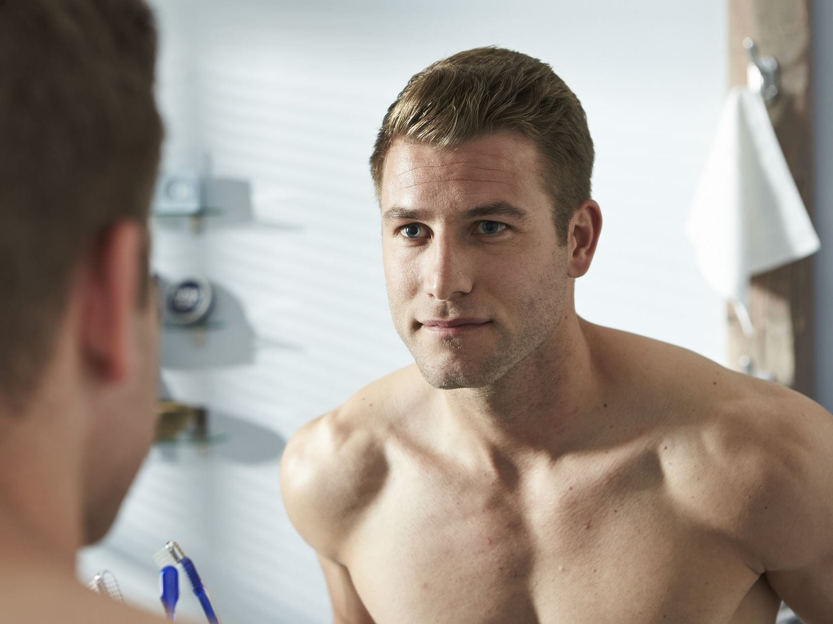 man with blonde hair looking at his reflection in the mirror