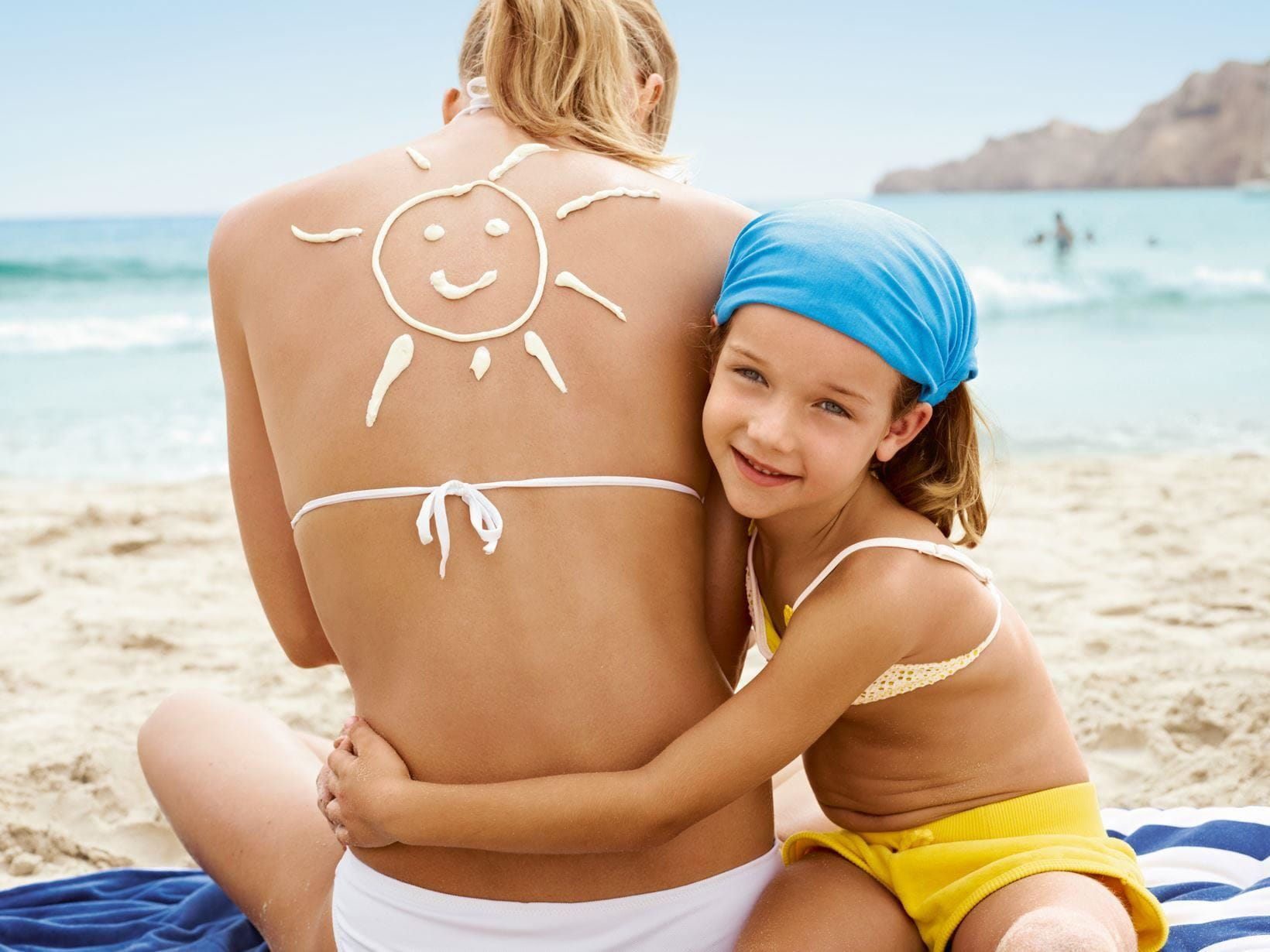 mother with sunscreen on her back and her daughter hugging her