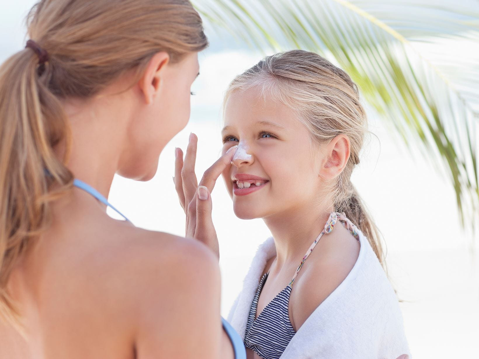 mother and daughter applying sunscreen