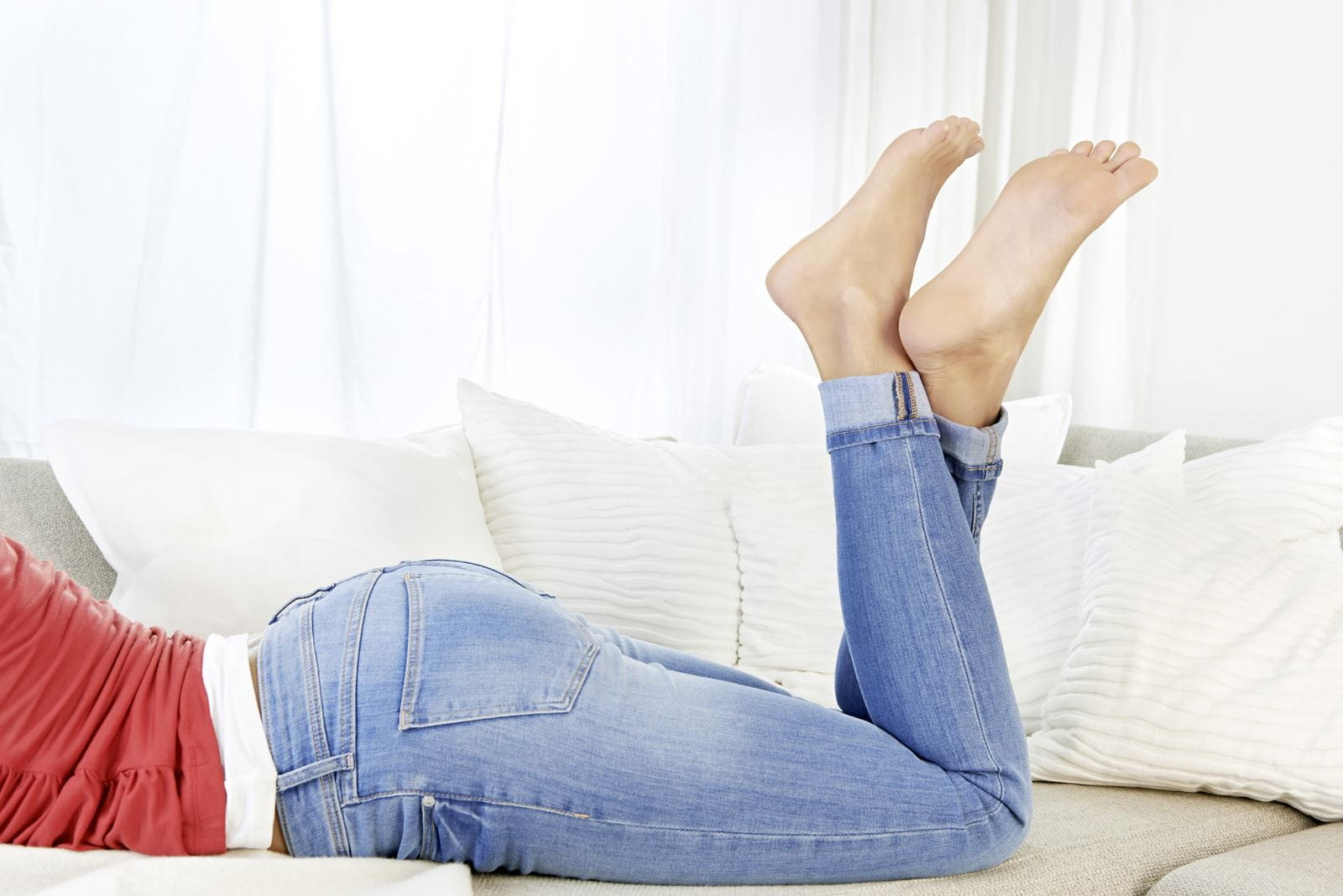 Woman lying on couch feet in air