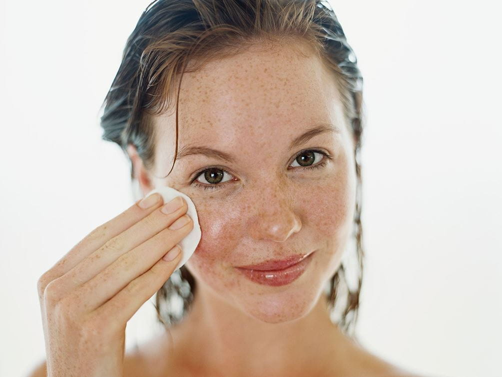 woman cleaning her face with cleaning pad