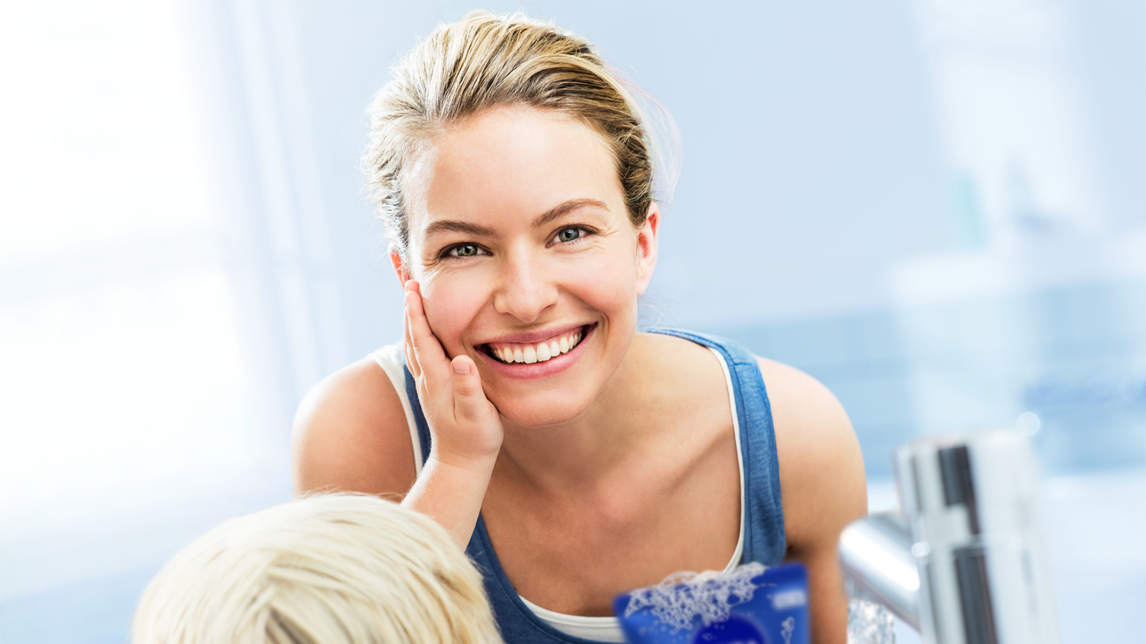 Blonde child touches smooth, soft cheek of mother in bathroom